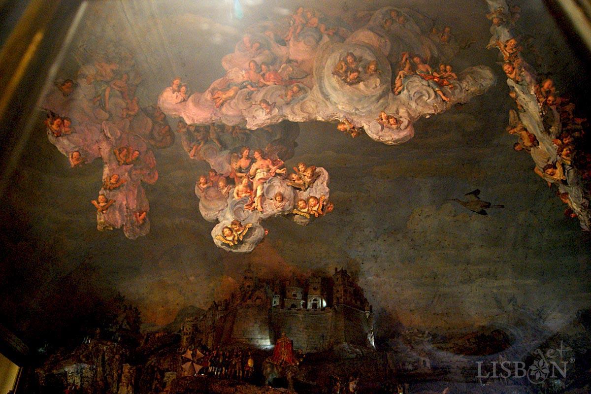 As nuvens suspensas, repletas de anjos e querubins, desenvolvem-se em vários planos criando dinamismo, profundidade e sentido cenográfico.