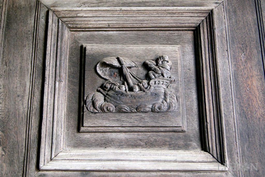As portas de madeira apresentam curiosos relevos que remetem para a lenda da origem da capela e para os atributos do santo.