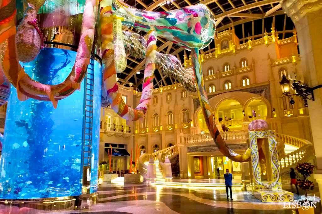 Grande Praça, Hotel MGM, Macau. De entre as fachadas dos edifícios é possível encontrar reproduções de emblemáticos monumentos de Lisboa, como a Estação Ferroviária do Rossio, a Casa dos Bicos ou ainda o Arco da Rua Augusta.