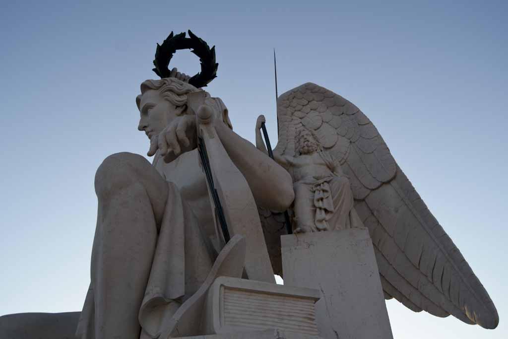 O deus Apolo, que apresenta livros e uma lira como atributos e a que se associa o Génio. Neste caso a figura do jovem imberbe está provida de asas, aspecto que o liga à figura cristã do Arcanjo São Miguel. De pequenas dimensões a discreta figura de um filósofo remete-nos, hipoteticamente, para Virgílio o escritor romano do séc. I a.C., que defendeu que na sequência das Idades do Mundo a última seria regida por Apolo.
