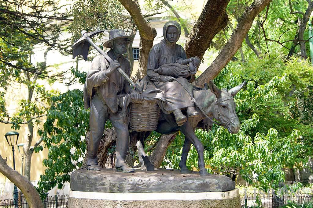 Conjunto Escultórico tributo ao povo e, em simultâneo, uma alusão à Sagrada Família. Casal de camponeses em bronze, composto por um homem que caminha a pé, transportando uma enxada ao ombro e uma mulher sentada num burro com um bebé ao colo.