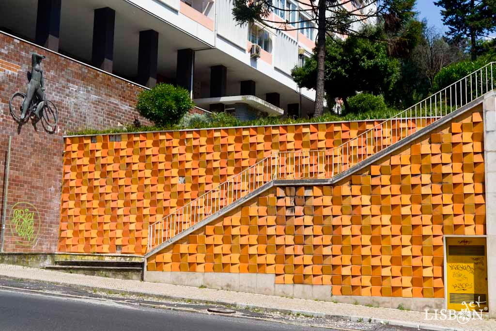 Ceramic panel by Eduardo Nery, Infante Santo Avenue. The use of ceramic slabs of three orange tones in a wedge shape allows different ways of placing them. Together with the reflection of light and the position of the observer, it creates unique visual effects.