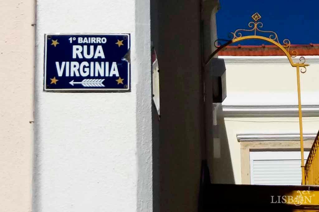 Placa toponímica da Rua Virgínia. Trata-se de uma chapa de metal rectangular, pintada de azul com letras brancas, em que cada canto apresenta uma estrela amarela de cinco pontas.