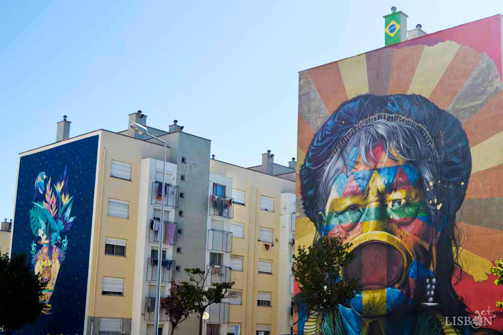 """From left to right: """"Oferenda"""" (offering) by the Portuguese artist Kruella D'Enfer; """"Raoni Metuktire"""", Brazilian indigenous leader of Caiapó ethnicity, portrayed by the Brazilian graffiti artist Kobra. Quinta do Marquês de Abrantes Neighbourhood."""