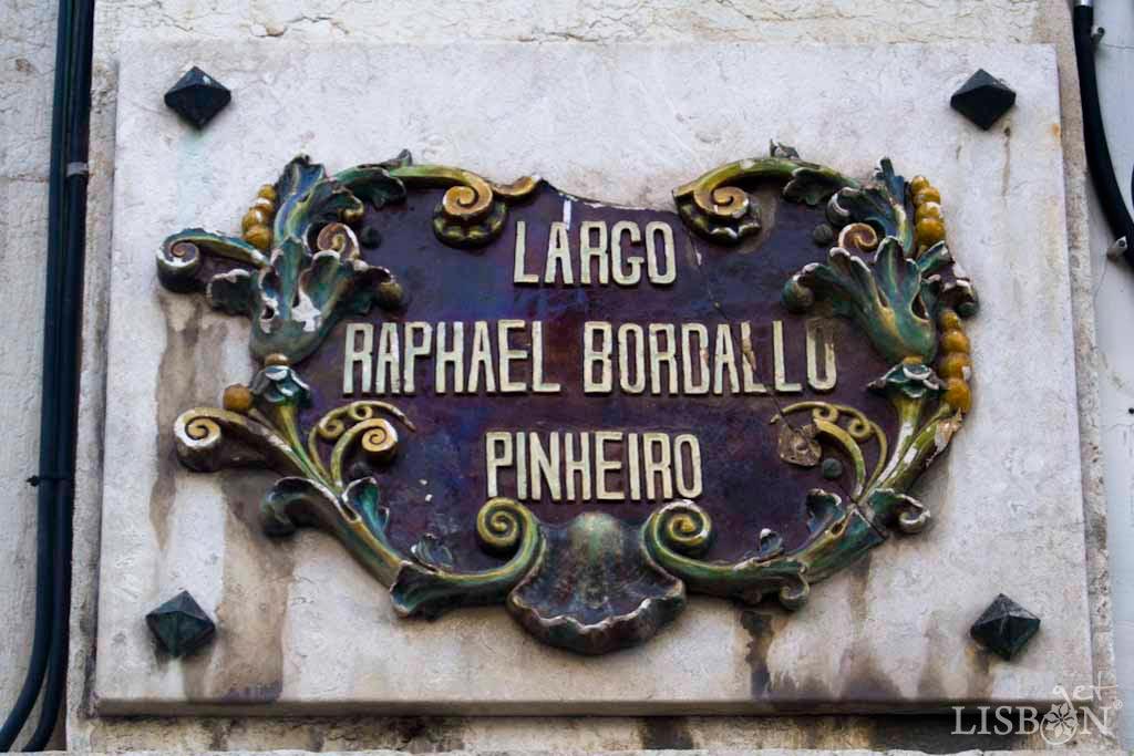 Placa toponímica do Largo Rafael Bordalo Pinheiro. As placas toponímicas em cerâmica, ali presentes, remetem para o seu trabalho como criativo ceramista que viveu e morreu no nº29, deste antigo Largo da Abegoaria.