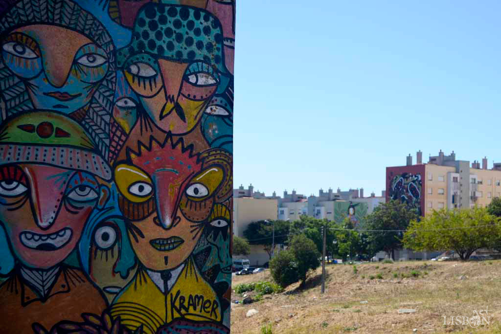 """Close-up of the Brazilian creator Kramer's, in Quinta do Chalé Neighbourhood. In the background, there's the Quinta do Marquês de Abrantes Neighbourhood where on the left we see """"Consejo del água"""" by the Ecuadorian artist Steep Aeon and on the right """"Amizade autêntica"""" (authentic friendship) by the Portuguese artist The Caver."""