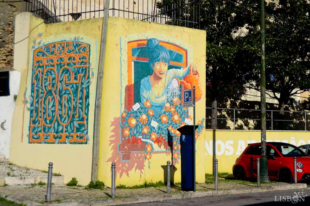 """This work by Portuguese artist Mário Belém is located at the intersection of Calçada de Santa Apolónia with Rua da Bica do Sapato. It consists of three parts: the date 1867, celebrated with life and color; the symbol of death and the inscription """"150 ANOS ABOLIÇÃO DA PENA DE MORTE EM PORTUGAL"""" (150 Years of the Abolition of the Death Penalty in Portugal)."""
