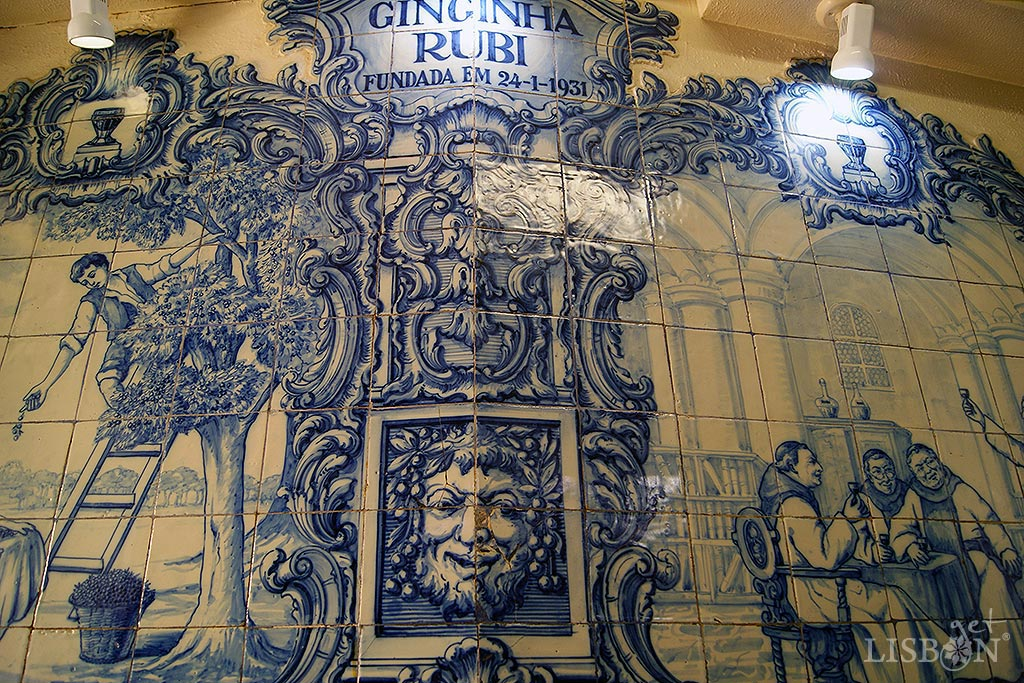 Ginjinha Rubi (1931) in Rua Barros Queirós. In this space are highlighted the joanine revivalist style, blue and white irregular-shaped tile panels. In the frames of volutes and shells, god Baco with an ironic expression and crowned with ginjas, looks at historical scenes where peasants collect this precious fruit and producers and friars taste the famous ginja liqueur.